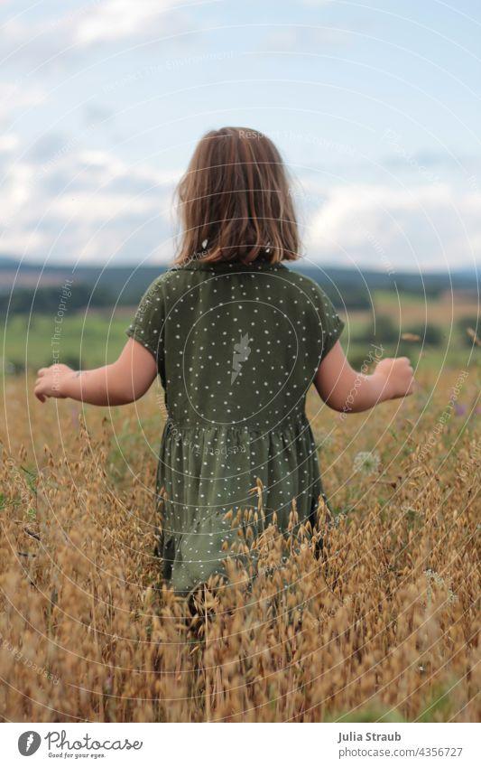 kleines Mädchen läuft mit geöffneten Armen durch ein Haferfeld haferfeld Körner Ähren hochsommer reif Kleid gepunktet kurze haare Rhön Natur alleine laufen