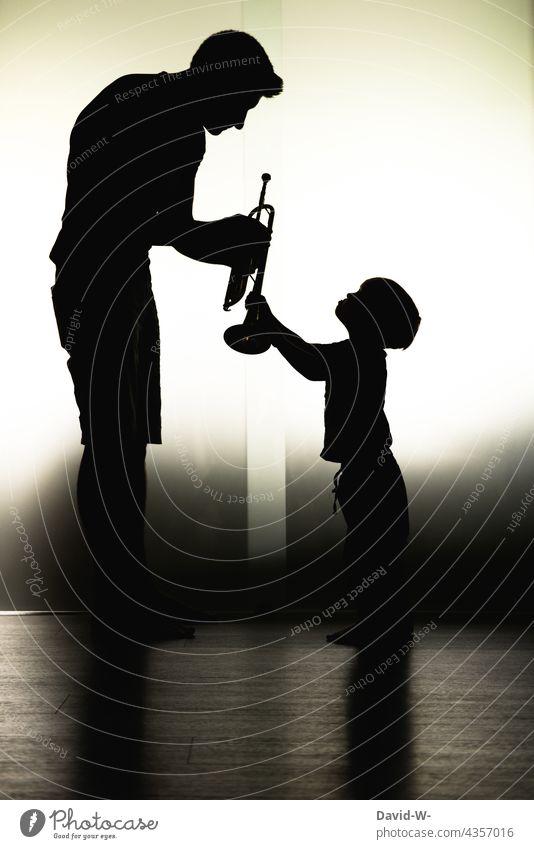 Vater und Kind - Kindererziehung - Fürsorge Papa Sohn Musik Instrument lernen zeigen Zusammensein Eltern gemeinsam Liebe Schatten Schattenspiel