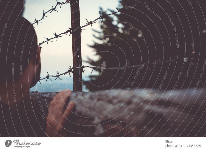 Mann Blick über einen Zaun mit Stacheldraht. Konzept Gefangen sein und Fernweh. gefangen Gefängnis Stacheldrahtzaun Grenze Barriere Sicherheit Freiheit Verbote