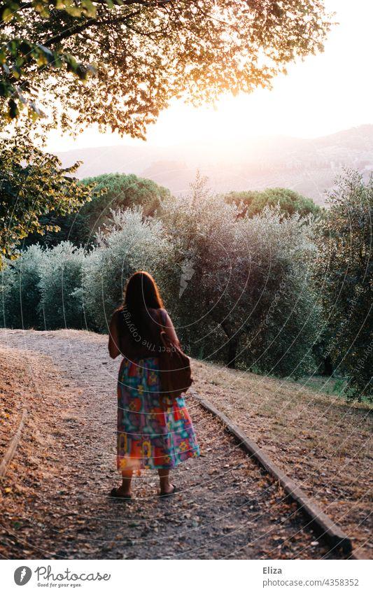 Rückansicht einer Frau mit buntem Rock in der Natur bei abendlichem Gegenlicht Abendsonne Abendlicht Sonnenlicht Aussicht Bäume Landschaft leuchtend Sommer