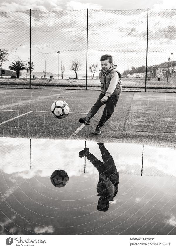 Junge kickt einen Ball auf schwarz-weiß Kind 1 jung Jugend Fußball im Freien außerhalb Park Straßenbelag schwarz auf weiß Bein rund Sport aktiv Lifestyle