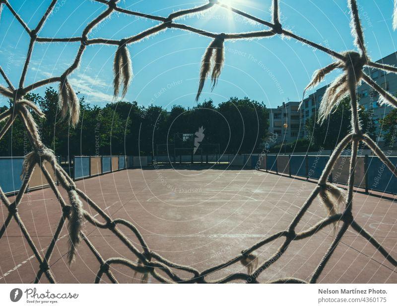 Gerahmter Blick durch ein Netz auf einen Fußballplatz in einer Nachbarschaft Entertainment Liga Sport Aktivität erfolgreich sein Tor Erfolg Rasen spielen Feld