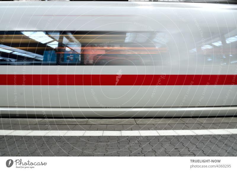 Ein schneeweisser ICE Zug mit einem dicken roten Streifen verlässt gerade München Hauptbahnhof. In seinen Fenstern spiegelt sich die Bahnhofshalle mit Neonleuchten, das graue Pflaster des Bahnsteigs zeigt einen weißen Streifenn-n-