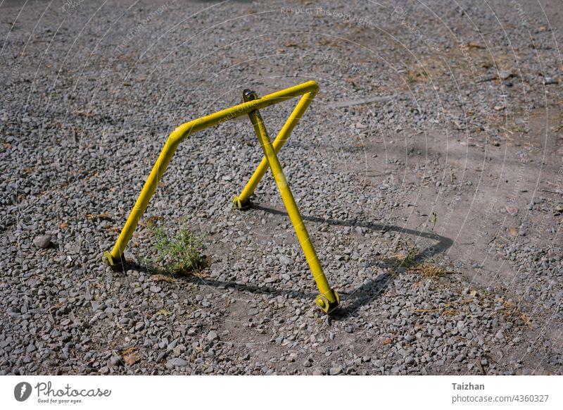 Gelber Metall-Parkstopper auf einem Privatparkplatz. Freies Parken Konzept parken Großstadt Auto Sicherheit stoppen Verkehr Transport Schloss urban Asphalt
