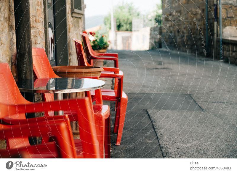 Rote Plastikstühle vor einem Café in einer italienischen Altstadt Stühle Gastronomie draußen Italien Gasse rot Straßencafé leer Terrasse Sommer Sitzgelegenheit