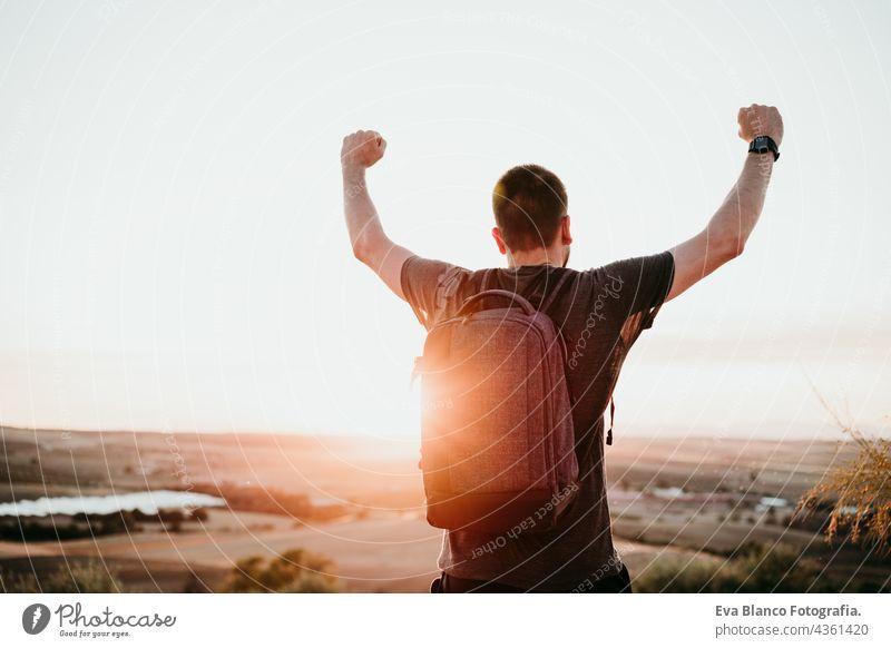 erfolgreicher Mann mit erhobenen Armen auf dem Gipfel eines Berges bei Sonnenuntergang stehend. Wandern und Natur Erfolg Backpacker Berge u. Gebirge wandern
