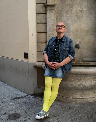 Mann im Jeansmini und gelben Strumpfhosen sitzt auf einem Brunnen und schaut zufrieden Mode Mode-Modell Lifestyle Stil Gesicht Rockträger Mensch Glück Stadt