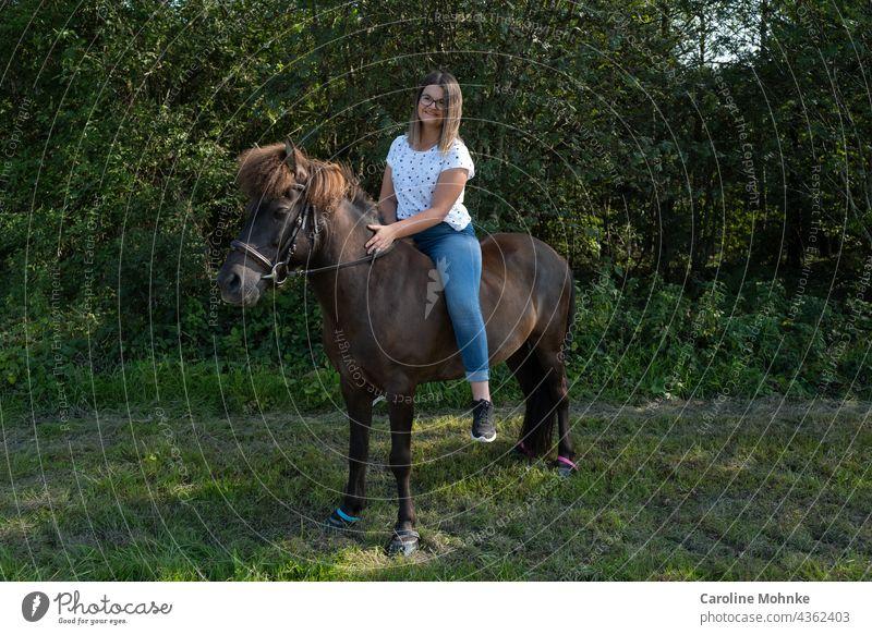 Junge Frau sitzt zufrieden auf einem Islandpferd Mensch Erwachsene Außenaufnahme Pferd Isländer Pony brünett 18-30 Jahre Farbfoto Blick in die Kamera langhaarig