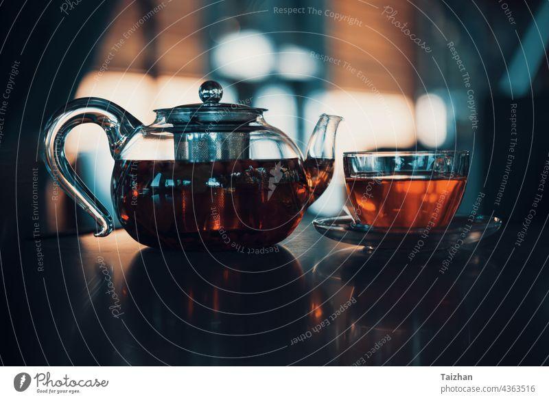 Beeren-Tee in einer gläsernen Teekanne in einem Café. Nahaufnahme Sommer Tisch Gesundheit trinken Glas Liebling Blatt Zitrone Minze rot Hintergrund Frühstück