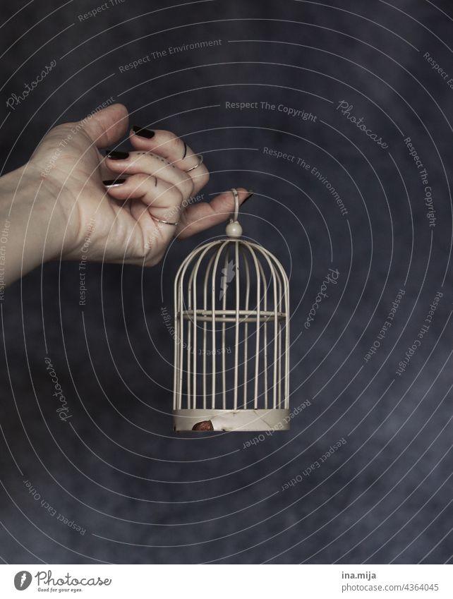 tätowierte Hand mit schwarzen Nägeln hält einen kleinen rostigen Käfig gefangen Tattoo Vogelkäfig geheim Geheimnis geheimnisvoll einsperren einengen