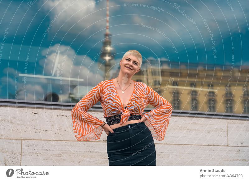 portrait einer jungen lächelnden frau mit dem berliner fernsehturm im hintergrund Frau Atelier selbstbewusst im Freien Berlin Fenster Spiegelung Stadt Großstadt