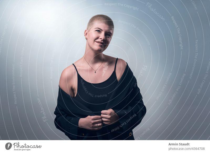 Studioaufnahme einer jungen, lächelnden Frau mit sehr kurzen blonden Haaren in schwarzer Kleidung Atelier selbstbewusst Behaarung Business Lächeln schüchtern