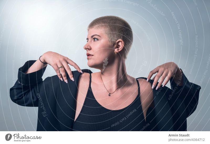 Studioaufnahme einer jungen, kräftigen Frau mit sehr kurzen blonden Haaren in schwarzer Kleidung Atelier ernst selbstbewusst Behaarung stark Kraft kampfstark
