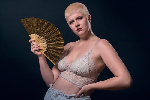 Studioaufnahme einer jungen, starken Frau mit sehr kurzen blonden Haaren, einem Fächer und einem Bustier Atelier ernst selbstbewusst Behaarung Kraft kampfstark