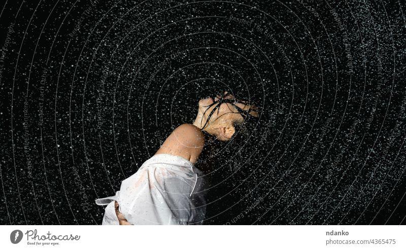 schöne Frau mit kaukasischem Aussehen und schwarzen Haaren tanzt in Wassertropfen auf schwarzem Hintergrund Person Tanzen Bewegung Tropfen platschen nass