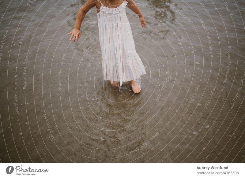 kleines Mädchen, das im Meer spazieren geht 0-5 5-10 Strand Kalifornien krause Haare fallen Familie Landschaft wenig im Freien Pazifikstrand Menschen Pier
