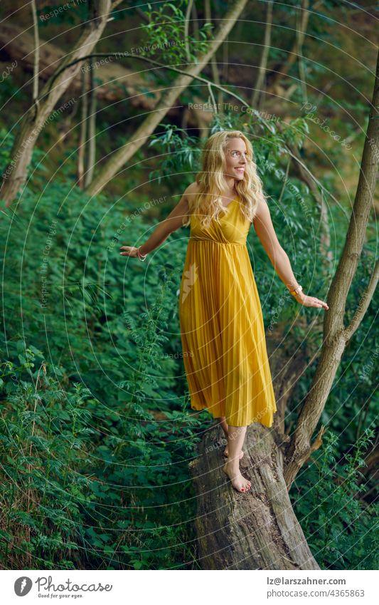 Unbeschwerte barfuß attraktive blonde Frau balanciert auf einem alten umgestürzten Baumstamm in einem Wald und trägt ein elegantes gelbes Kleid, das mit einem glücklichen freundlichen Lächeln zur Seite schaut