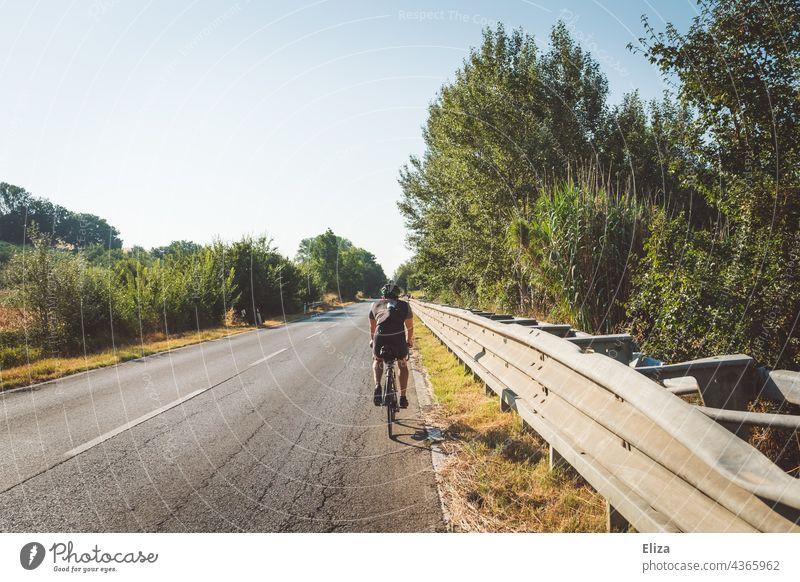 Rennradfahrer in Sportbekleidung fährt mit seinem Fahrrad auf einer italienischen Landstraße Fahrradfahrer Italien mediterran Sommer Urlaub Fahrradfahren