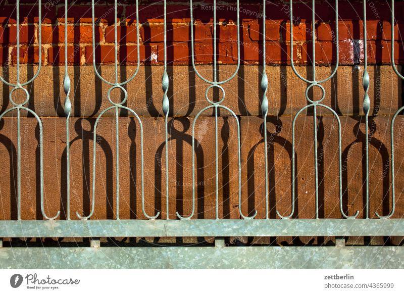 Schmiedeeiserner Zaun zaun eisen schmiedeeisern stahl dekor schmuck tür tor rolltor licht schatten verstrebung bandstahl mauer mauerwerk sicherheit geschlossen