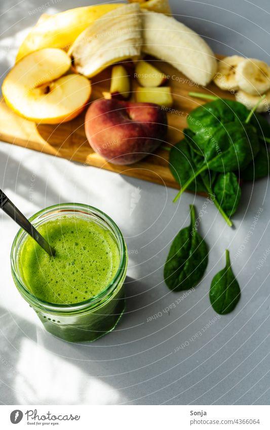 Grüner Smoothie in einem Trinkglas und Zutaten auf einem Holz Schneidebrett smoothie grün Obst Gemüse Vegetarische Ernährung Gesunde Ernährung selbstgemacht