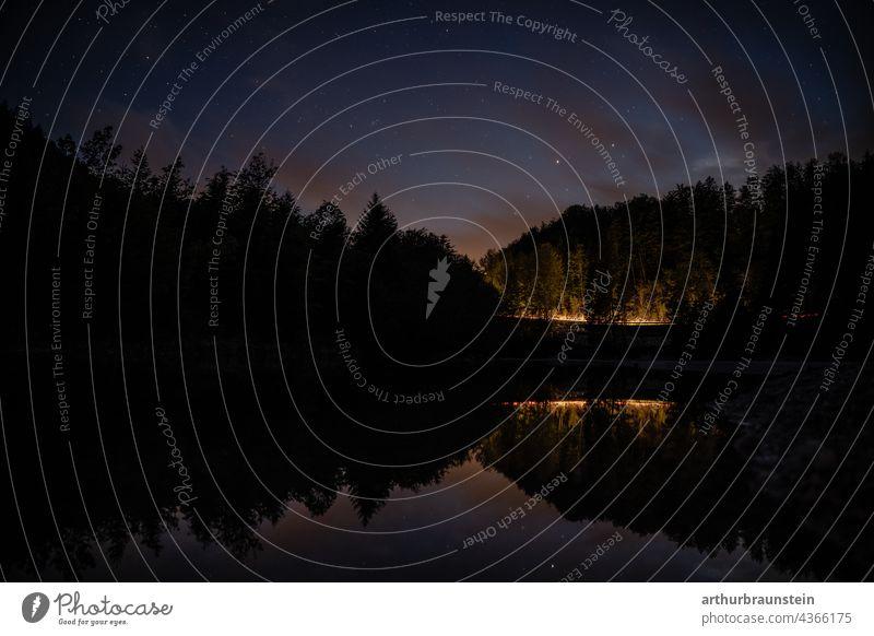 Nachtaufnahme von ruhigem Wasser unter Sternenhimmel mit Autolichtern in der Ferne im Wald natur Außenaufnahme Menschenleer Landschaft nacht see wasser sterne