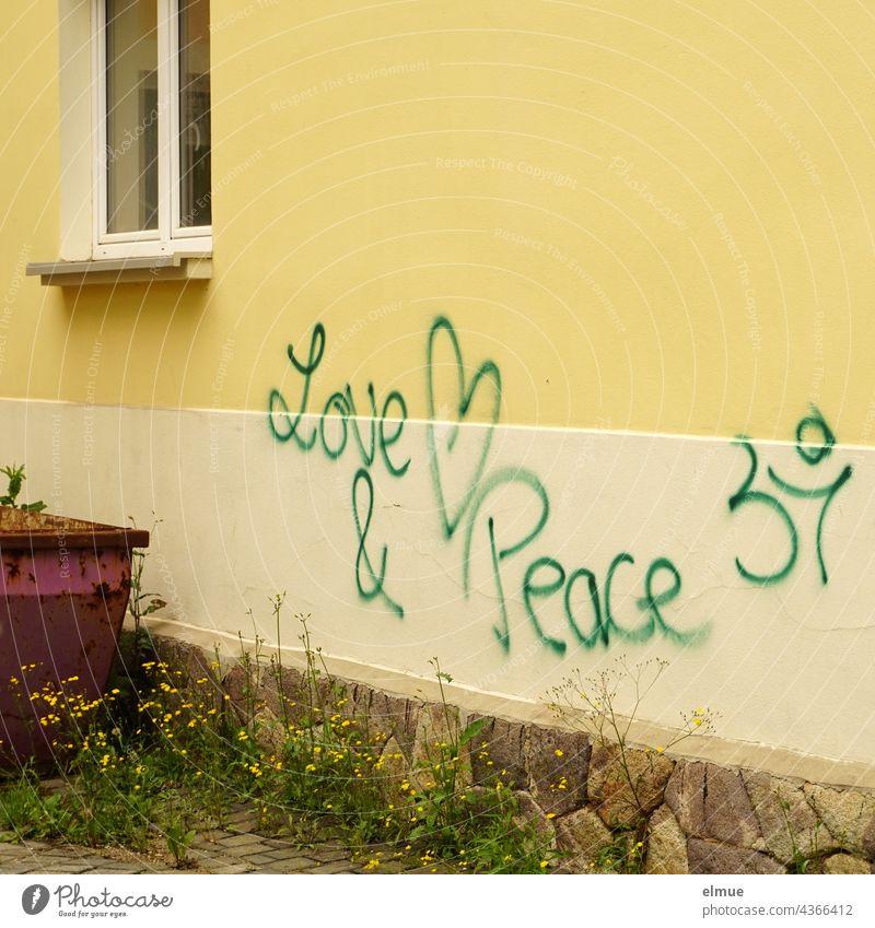 Love & Peace steht in grüner Schrift an einer gelben Hauswand neben einem abgestellten Container / Graffito love and peace Liebe Frieden Graffiti Schmiererei