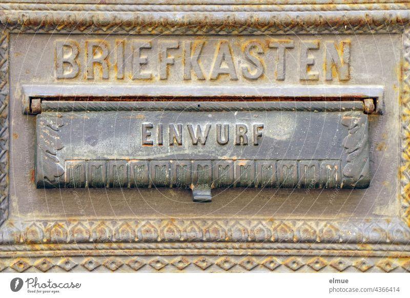 Teilansicht eines gusseisernen Postkastens mit Verzierungen und der Aufschrift BRIEFKASTEN sowie einer Einwurfklappe mit EINWURF / Briefwechsel Briefkasten Guss