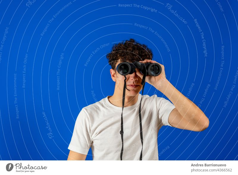 Junger Mann auf isoliertem blauen Hintergrund, der mit einem Fernglas in die Ferne schaut jung Golfloch Humor vereinzelt Aussehen Blick Model OK Person photogen