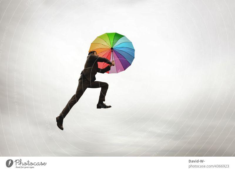 Mann fliegt mit dem Regenschirm Freiheit fliegen schweben Schwerelosigkeit bunt Himmel aufsteigen Leichtigkeit Business Anzugträger Erfolg konzept