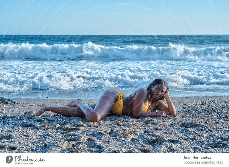 Afroamerikanische Frau liegt auf dem Sand am Strand mit Meereswellen im Hintergrund Afrikanisch Amerikaner Lügen MEER Wellen Afro-Look sich[Akk] entspannen