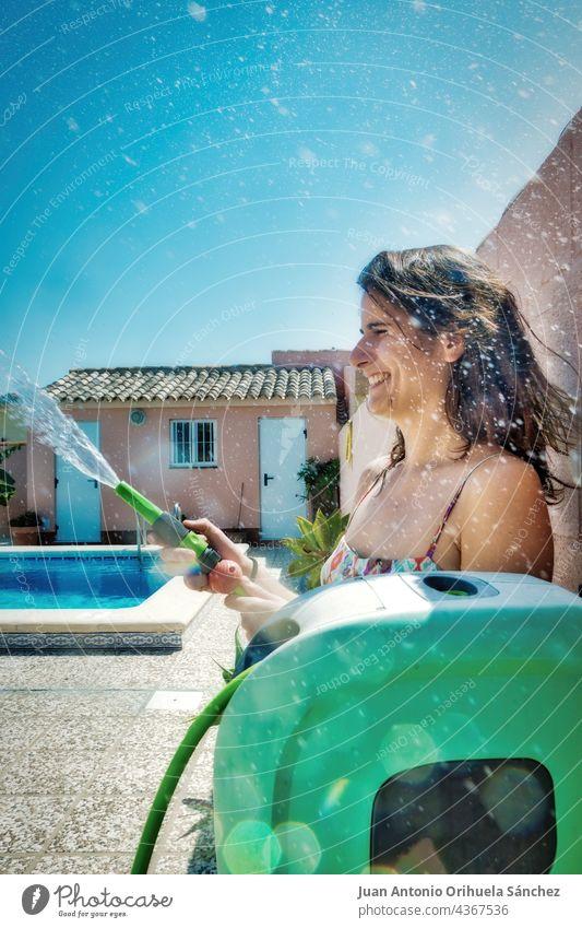 Hübsches Mädchen hat Spaß daran, Wasser mit einem Schlauch zu werfen. hübsch nass platschen Haus Tropfen sonnig Saison Sommer Geplätscher erfrischend Glück