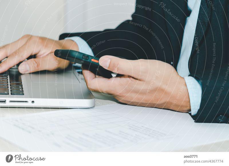 Geschäftsmann hält Smartphone und Computer-Laptop. Business Büro Technik & Technologie Menschen Mann Hand Schreibtisch online Person Telefon Internet Arbeit