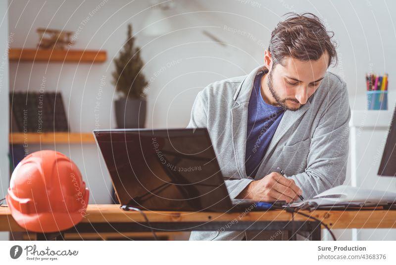 Der Designer dachte nach und neigte den Kopf, während er mit Zeichnungen und Computern an dem Tisch arbeitete, auf dem der Helm lag. Farbe abgestuft