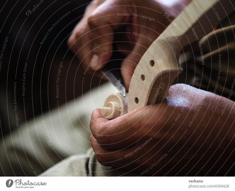 Geigenbauermeister mit einem Messer beim Schnitzen eines Geigenkopfes und einer Schnecke des Modells Stradivarius Zupfinstrumentenmacher Bratsche Herstellerin