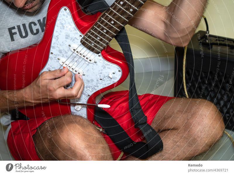 Unbekannter Mann sitzt auf dem Boden und spielt eine rote E-Gitarre. Gitarrenspieler spielen Person unverschämt männlich Felsen Punk lässig alternativ Musiker