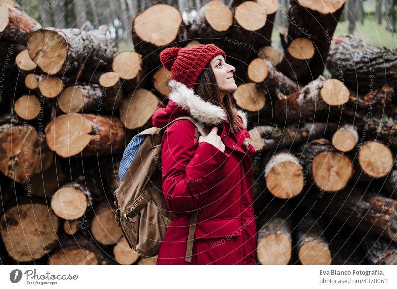 Backpacker Frau vor Holzstämmen in den Bergen. Herbst- oder Winterzeit. Natur und Lebensstil wandern Berge u. Gebirge Kaukasier Wald kalt Mantel Hut Camping