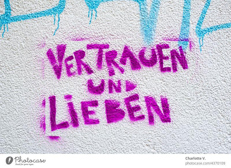 Vertrauen und lieben Graffiti Farbfoto Außenaufnahme Wand Schriftzeichen Mauer Straßenkunst Schmiererei Jugendkultur Subkultur Buchstaben trashig Text Wort