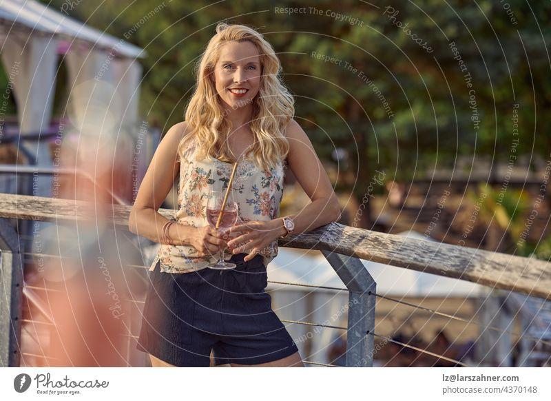 Hübsche, entspannte blonde Frau, die im Sommerurlaub einen tropischen Cocktail genießt, an ein Holzgeländer gelehnt steht und mit einem freundlichen Lächeln in die Kamera schaut