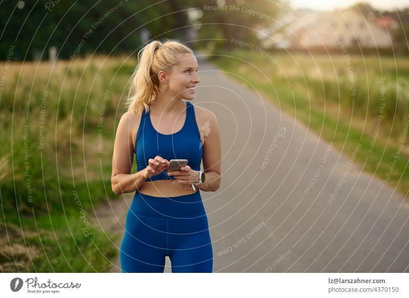 Fitte, sportliche Frau, die beim Joggen auf einem ländlichen Wanderweg ihr Handy konsultiert und dabei mit einem zufriedenen Lächeln zur Seite schaut passen