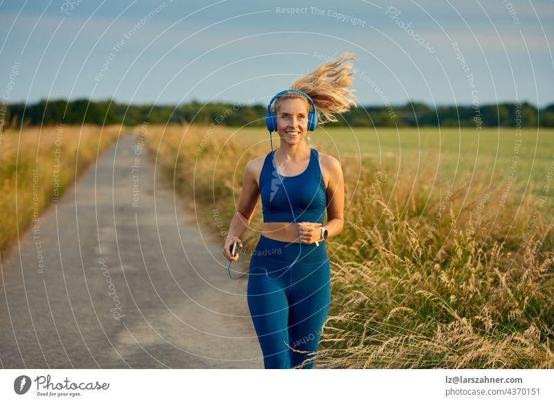 Eine fitte, lebhafte junge Frau, die auf einem Fußweg in einem offenen Feld joggt, nähert sich der Kamera mit einem glücklichen Lächeln und einem nach hinten fliegenden Pferdeschwanz in einem gesunden, aktiven Lebensstilkonzept.