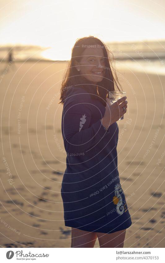 Frau genießt den Sonnenuntergang an einem tropischen Strand, während sie einen Cocktail trinkt und sich umdreht, um mit einem fröhlichen, lebhaften Lächeln über ihre Schulter in die Kamera zu schauen