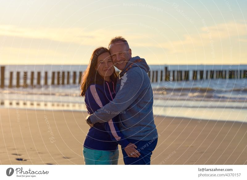 Glückliches romantisches Paar mittleren Alters genießt eine liebevolle Umarmung an einem verlassenen tropischen Strand bei Sonnenuntergang und lächelt in die Kamera mit Kopie Raum