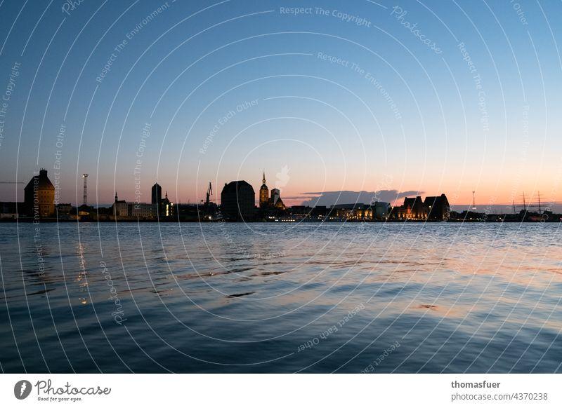 Silhouette von Hafenstadt bei Sonnenuntergang Gegenlicht Stimmung Dämmerung Abend Lichterscheinung Horizont Ruhe reisen Sommer Himmel Küste Ufer Meer Stadt