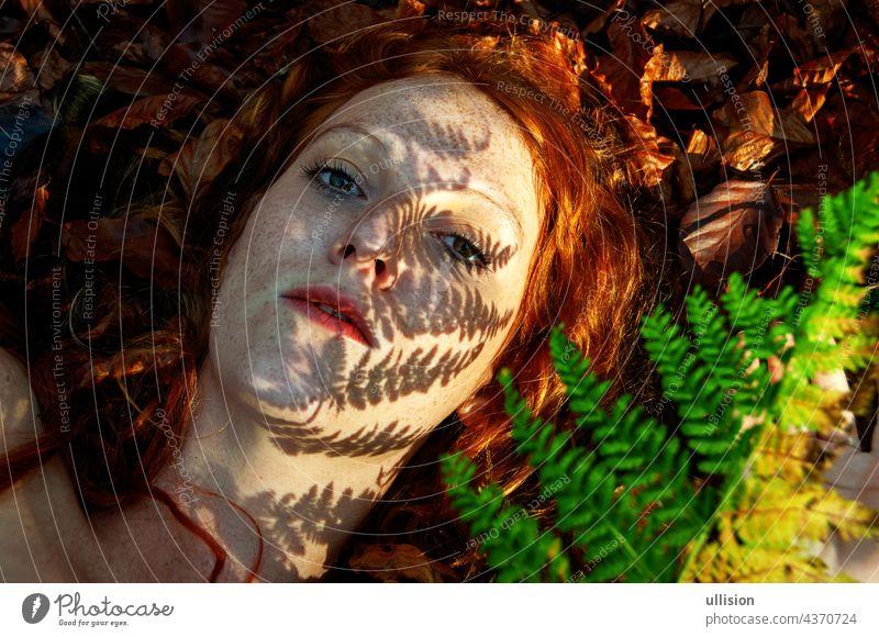 schönes Porträt eines jungen verführerischen fuchsigen Mädchens im Herbst, mit Schatten des Farnwedels im Gesicht, schöne sexy attraktive rothaarige Frau