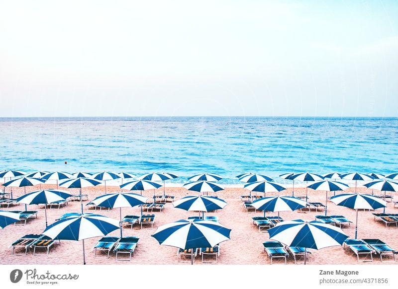 Liegestühle und Sonnenschirme am leeren Strand Sonnenbänke Sonnenbank leerer Strand Sommerurlaub Sommerreise Europa Griechenland Italien Bräune Bräunen
