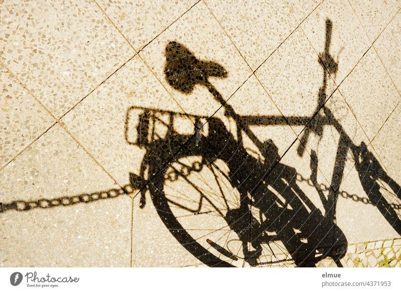 Schatten eines Herrenfahrrades und einer Absperrkette auf einem Gehweg / Fahrradfahren Herrenrad Kette Fußweg radeln Absperrung Sattel Radstange parken