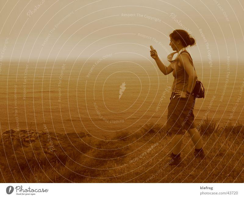 Call the Sea Frau Meer Strand ruhig Wiese Küste Telefon leer Handy festhalten Mobilität Fotograf Fotografieren Sepia Klippe Momentaufnahme