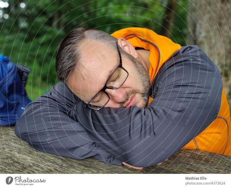 Mann mit Brille schläft und ruht sich aus ausruhen liegen schlafen Erholung Sommer Ferien & Urlaub & Reisen erledigt daypack Rucksack Tasche ausschlafen reisen