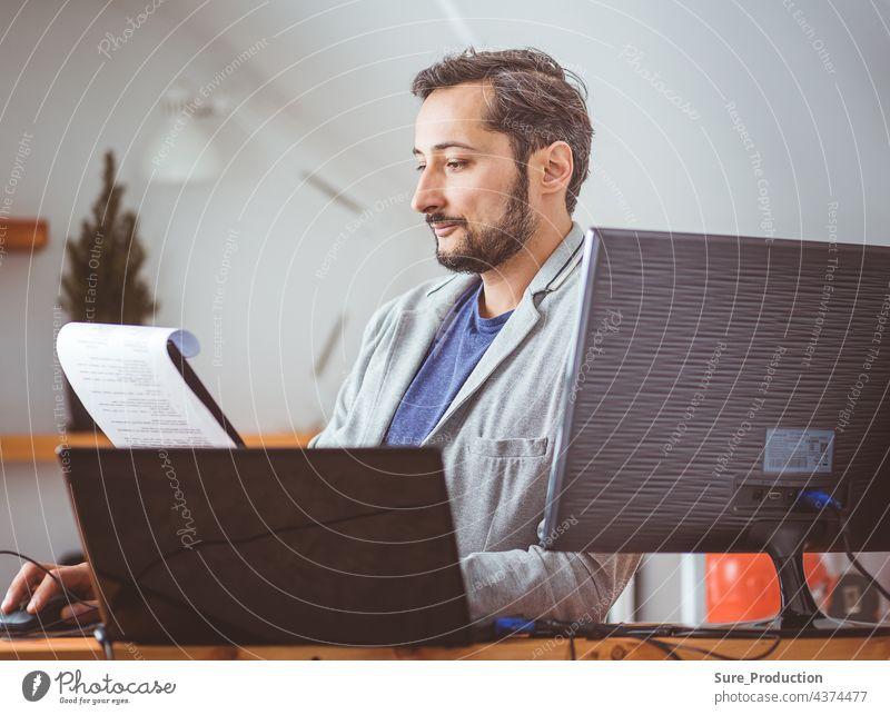 Ein Mann im Raum studiert die Dokumente. Ein Mann in Freizeitkleidung an einem Laptop. Aus der Ferne arbeiten Business Computer Schriftstück Geschäftsmann