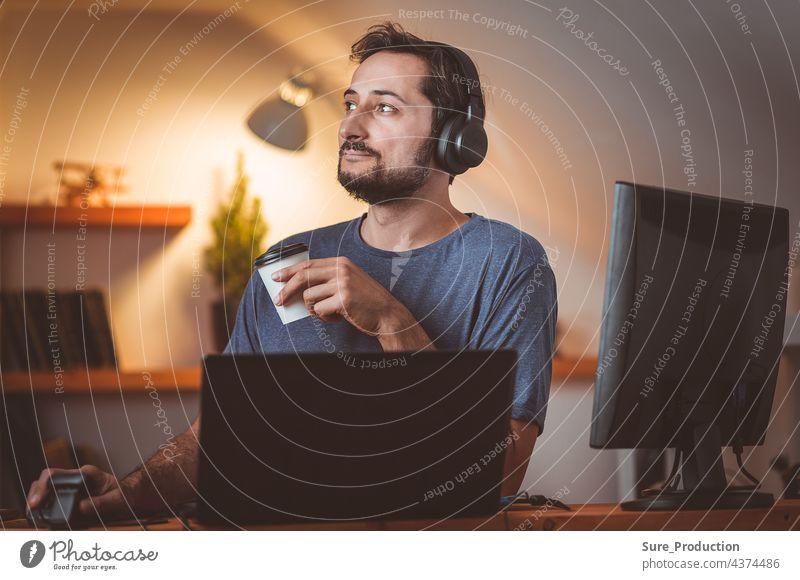 Ein Student mittleren Alters mit Bart beschäftigt sich am Abend mit Kopfhörern und Kaffee Universität Wissen Wissenschaft Dissertation Arzt Meister Bildung
